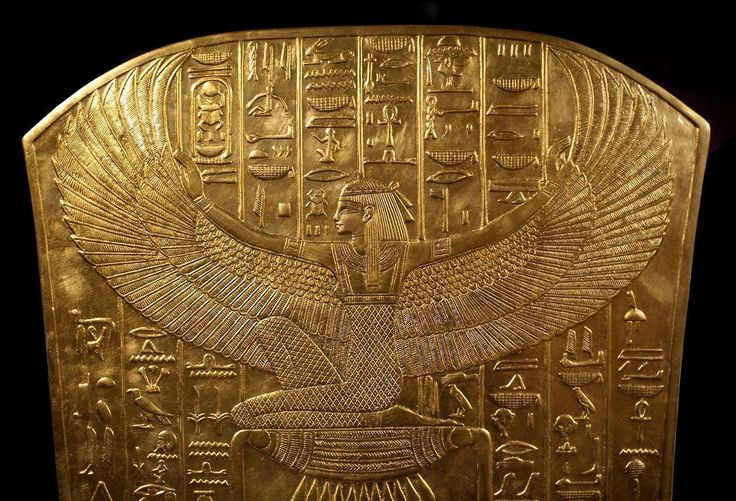 """Detail from one of the coffins of King TutankhAmon (now in the Cairo Museum): the Goddess Isis with outstretched wings and kneeling on the hieroglyphic symbol for """"gold"""""""