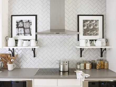 One of the easiest ways to mix up your kitchen's backsplash design is by laying tile in a fun, unexpected pattern, such as this herringbone design featured in HGTV Magazine. By pairing the design with simple shelves and black-and-white art, the charming tilework remains the star of the space.