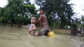 Children walking through flood water in Pathein, in the Irrawaddy delta region of Burma, 21 August 2012 #savemyanmar