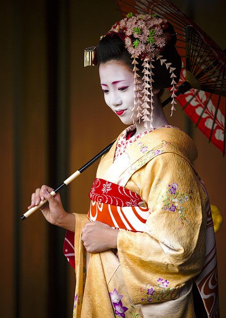 A junior maiko. Her lower lip is only painted and the long silk petals point to her rank.