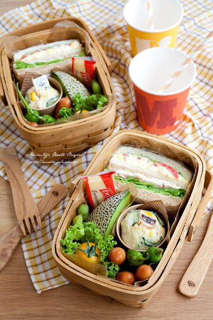 Sandwich of tomato and cucumber and egg, sandwich of roasted chicken and lettuce, potato salad, sausage, melon, tomato, and edamame.