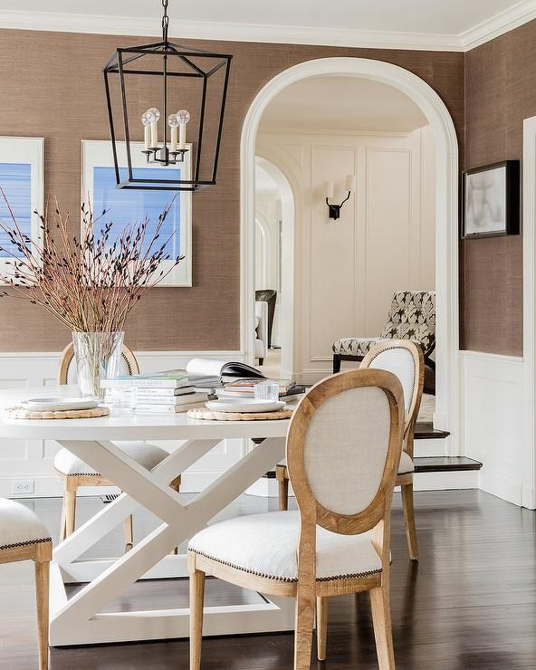 Welcoming white and brown dining room is lit by a Darlana Medium Lantern hung above a round white dining table seating French round back dining chairs in front of a white wainscot wall lined with brown grasscloth wallpaper.