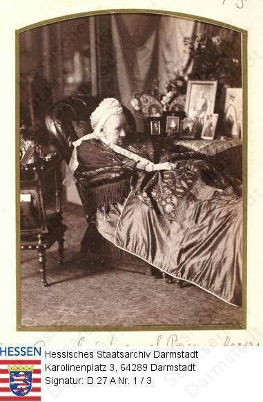Very rare photo of Queen Victoria lying on a chaise, next to photos of her family. Notice the largest photo is of her late husband, Prince Albert.