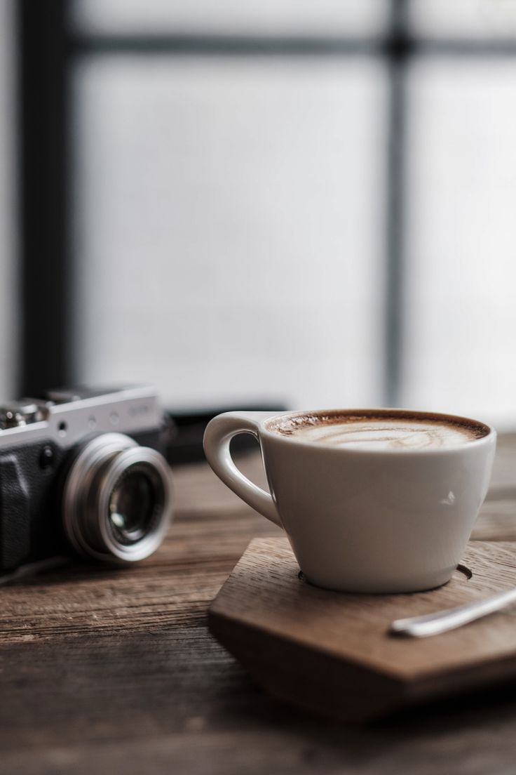 Cup of coffee, camera and beautiful rustic wooden table.                                                                                                                                                                                 More