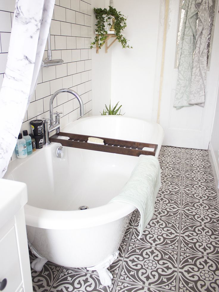 Grey and white tiles, white claw foot tub, marble shower curtain, hanging plants, subway tile.