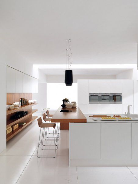 Thin white kitchen worktop with chunky wooden bfast bar.
