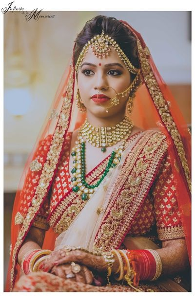 red lehenga, red net dupatta, brocade blouse, red chooda, gold mathapatti, polki choker, emerald raani haar