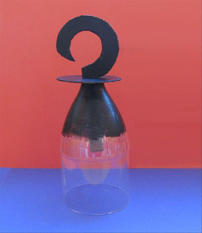 """Haak gemaakt van de bovenkant van een plastic fles. In de hals wordt dan de haak ( met een """"steel"""" om aan vast te houden) bevestigd."""