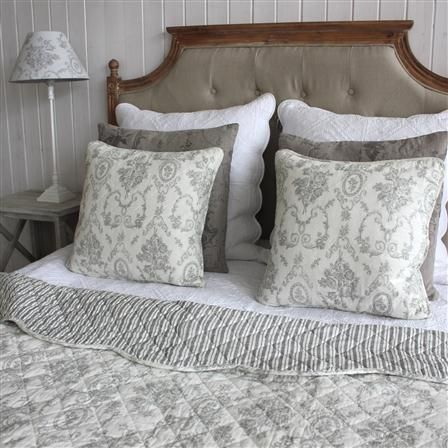 Turned back quilted grey bedspread and coordinating cushions by ACHICA.