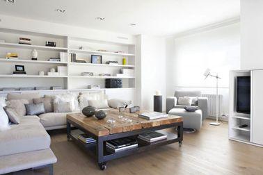 Déco salon en dégradé de gris et blanc avec grand canapé d'angle gris perle, table basse esprit industriel en bois et métal. Le fond de la b...