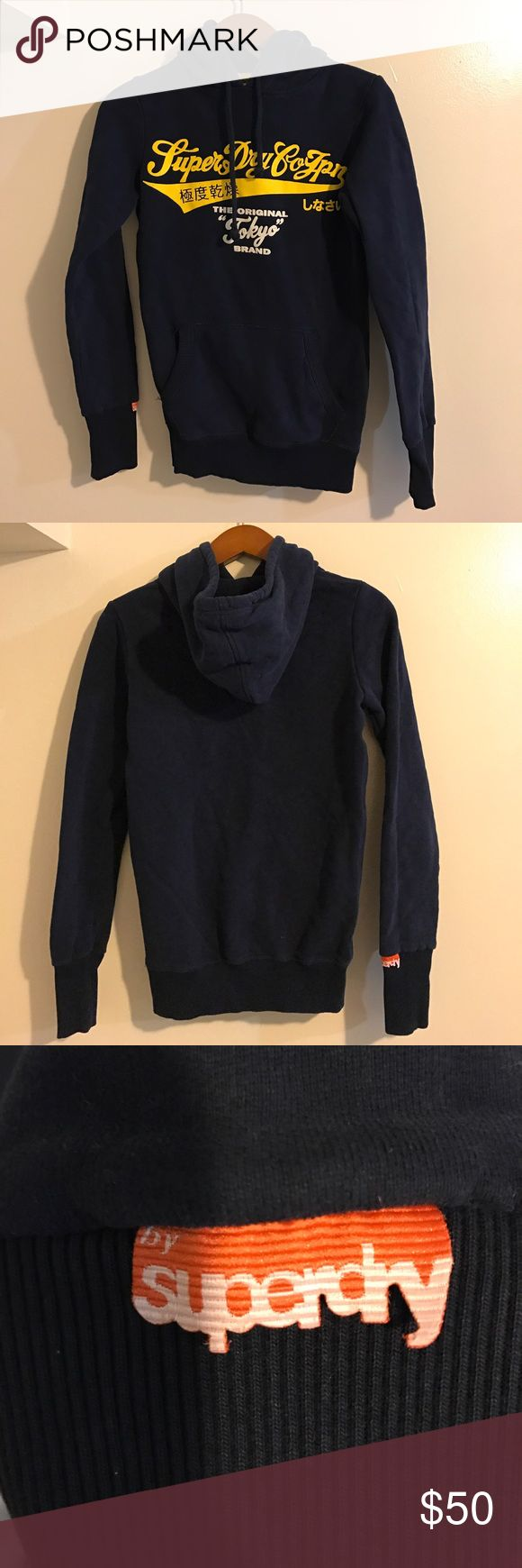 Superdry hoodie Worn once/ navy hoodie with yellow and white lettering/ one middle two way pocket/ orange superdry logo on end of sleeve Superdry Tops Sweatshirts & Hoodies