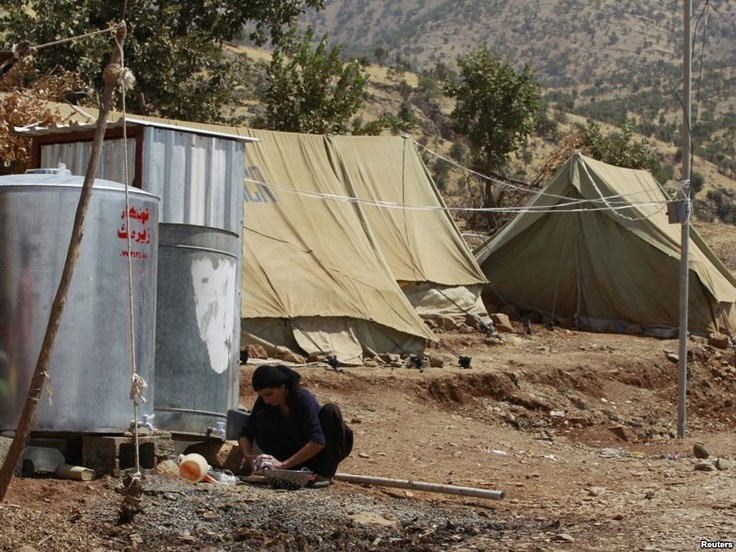 A woman washes dishes at a refugee camp near Qandil Mountain, a border zone in northeastern Iraq where Kurds have fled offensives in Turkey and Iran.