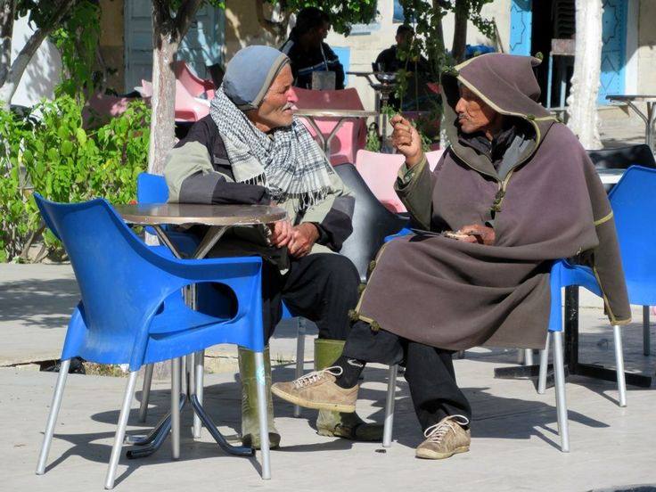 A pair of elderly Tunisian men lounge at a cafe on El Bathaa Square in Testour, Tunisia.