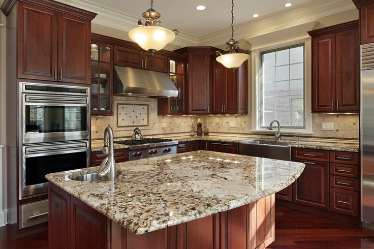 Luxury kitchen with mahogany cabinets and a granite island complete with sink. Pendant hanging lights give the kitchen an elegant look.