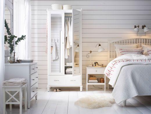 Et stort soverom i landlig stil med en garderobe med speildører, en kommode med speil oppå, et nattbord og ei stor seng, alt i hvitt.