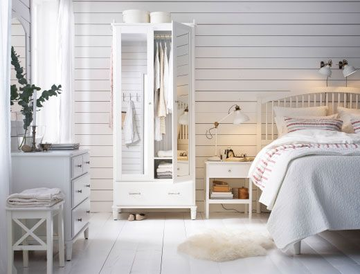 Camera da letto in stile country con guardaroba con ante a specchio, cassettiera con specchio, comodino e letto, tutto in bianco.