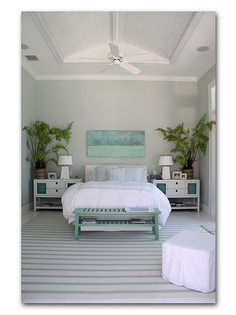 lovely take on a modern coastal bedroom with nautical stripes, lots of white, popped with palms & greens, ceiling fan and white linens