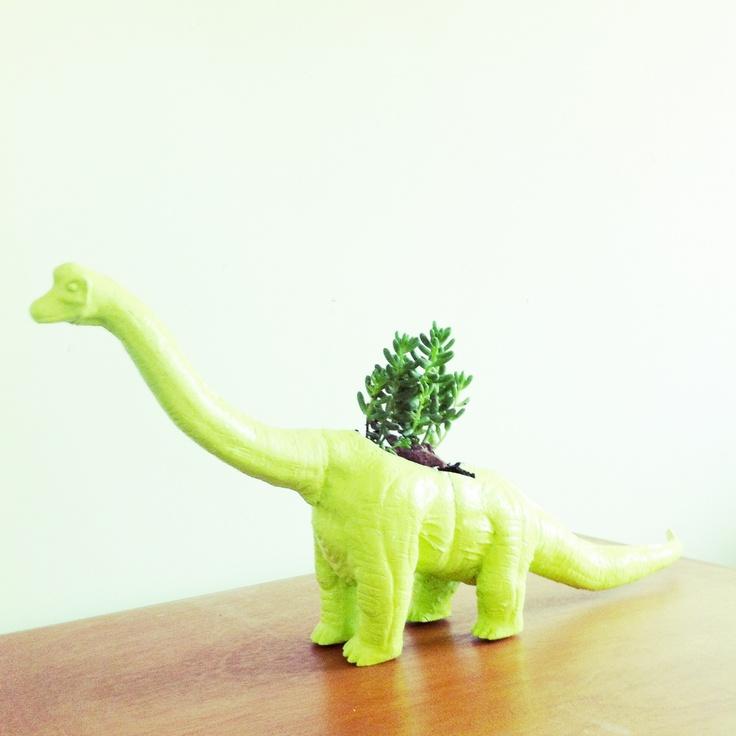 Dinosaurio de maceta con suculenta color verde fosforescente :D !!! Tenemos mas dinosaurios como triceratopos y T-rex color naranja y violeta :)