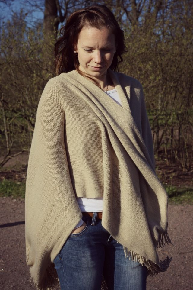 Camel colored poncho and blue jeans