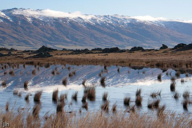 We took this shot on our recent trip to the South Island in Central Otago. The water you see in the foreground is not a pond or a lake, it is a depression in the ground, where the water has collected during winter.   This is why we can see the rushes in the water. The water would be no more than a few inches deep and will dry out and return to farm land very quickly. But for us it makes a nice photo.