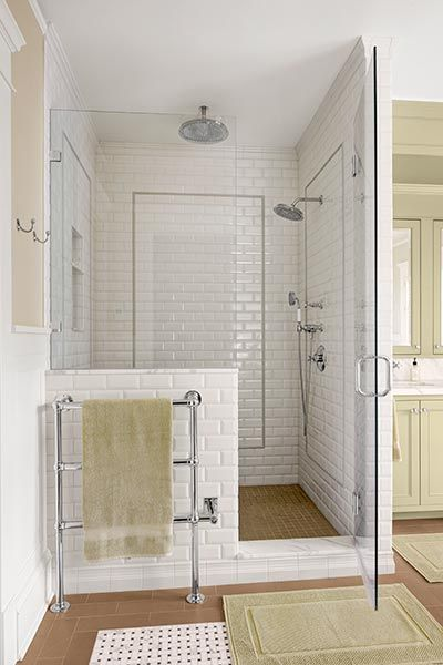A half-wall of subway tile lends a touch of privacy. The wall- and ceiling-mounted showerheads of this master bath operate independently of each other. A towel warmer gives an extra touch of luxury to the shower ritual without consuming much energy.