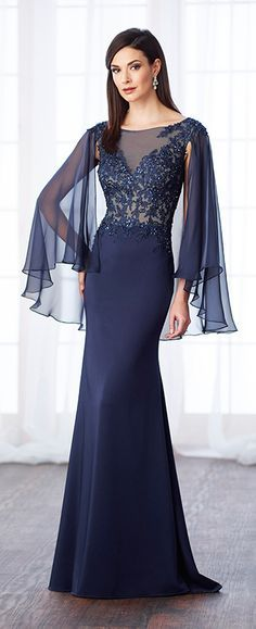 Satin crepe, chiffon, and lace fit and flare gown with bateau illusion neckline, hand-beaded lace sweetheart bodice, attached cape with back keyhole creates draped three-quarter length sleeves, sweep train.