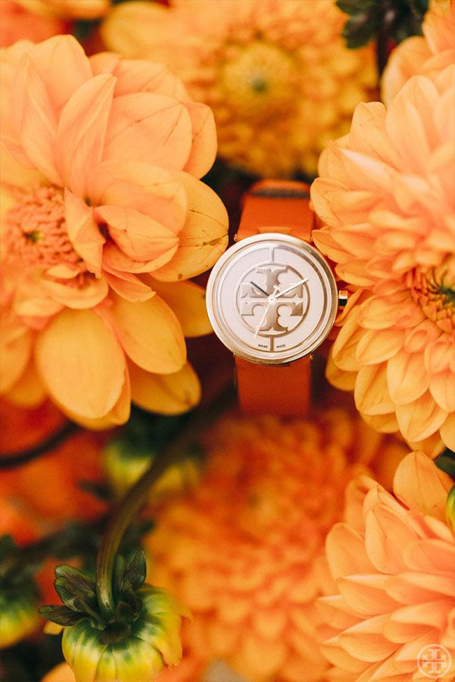 The orange Reva Watch — named after Tory's mother — and a bouquet of orange blooms, by Noa Griffel