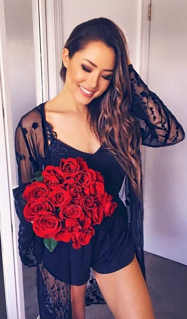 #spring #outfits woman in black spaghetti-strap rompers holding bouquet of red rose. Pic by @hapatime