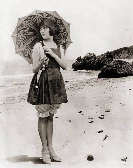 PHOTO – LIKELY FOR ARCADE CARD – MOVIE STAR – LILA LEE – ON BEACH WITH PARASOL AND LONG SWIM SUIT