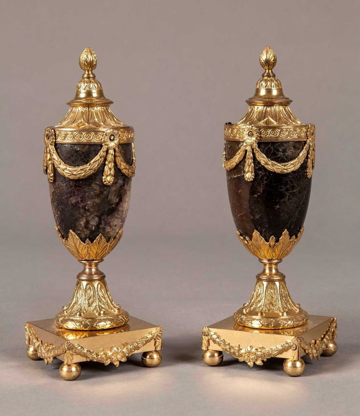A Pair of Blue John Cassolettes By Matthew Boulton Constructed in gilt bronze and Derbyshire Blue-John fluorspar; the square bases are supported on ball feet, the ovoid bodies enwrapped with swags and garlands, with conical covers; reversible to form a pair of candlesticks. Circa 1775 Artist Biography: Matthew Boulton (1728-1809) is rightly recognised as the pre-eminent English manufacturer of ormolu and objets de luxe in the late 18th century. Often incorporating highly prized specimens of…