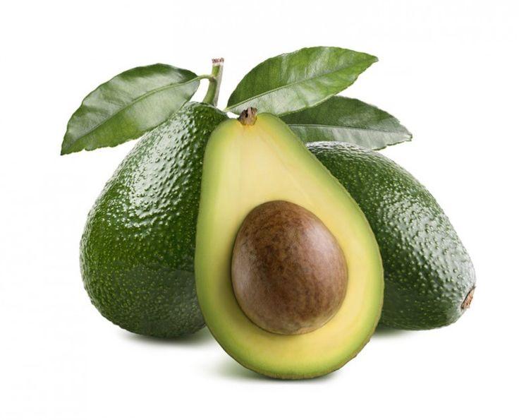 zwei unreife grüne Avocado mit Blättern am Stiel und eine halbe aufgeschnittene Avocado mit Avocadokern