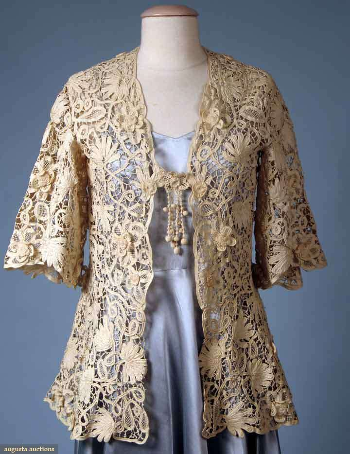 "CREAM HANDMADE LACE JACKET, c. 1910 All-over intricate Battenburg pattern, scattered 3-D flowers w/ crochet rosette centers, short bell sleeves, V-neck, crochet ball fringe over single closure, B 37"", FL 25"", BL 28"", excellent. Brooklyn Museum Augusta Auctions"
