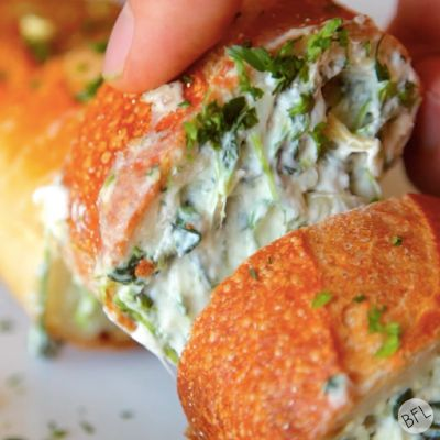 Garlic bread stuffed with spinach artichoke dip -- a perfect appetizer, or side for an Italian meal.