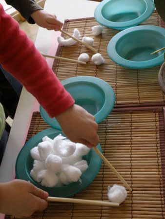 Transfer cotton balls from one bowl to another with chopsticks. New cool idea for working on fine motor muscles and hand eye coordination. Easy to set up and mess-free. Read more at: http://www.playbasedlearning.com.au/2010/08/chopstick-fun/