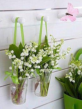 Maak dit vrolijke hangertje zelf na! Door twee plastic bekertjes met een lint op te hangen, te vullen met wat water en doe er dan wat lelietjes van dalen in.