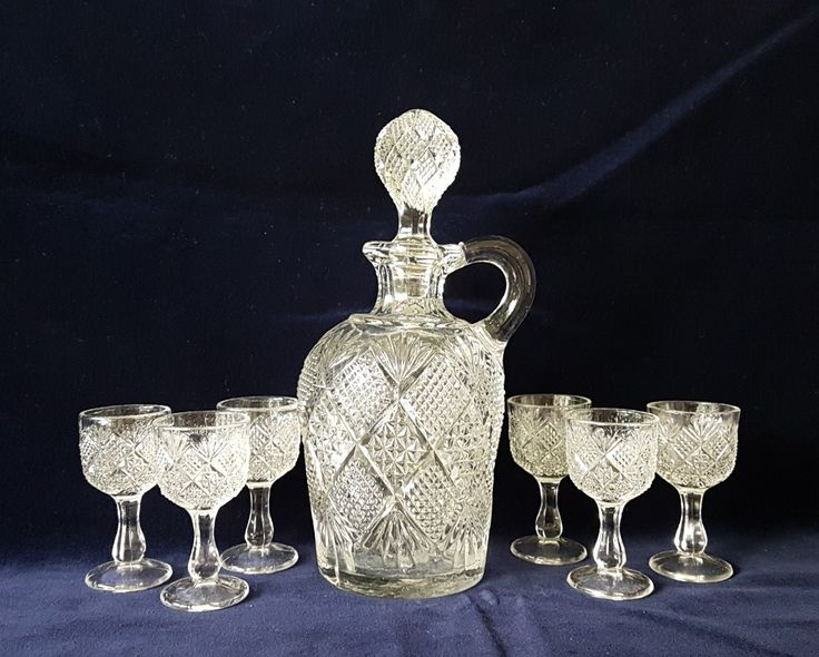 An early American pressed flint  glass whiskey jug/decanter with it's original six shot glasses. Made by the model flint glass company , Albany  IN : 1893 - 1899