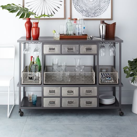 The metal on the Industrial Rolling Bar Cart is acid-washed, sandblasted and finished with an electroplating process that gives it a vintage appearance. Its drawers and shelves provide plenty of storage space, and its roomy surface is perfect for displaying all your home bar supplies.