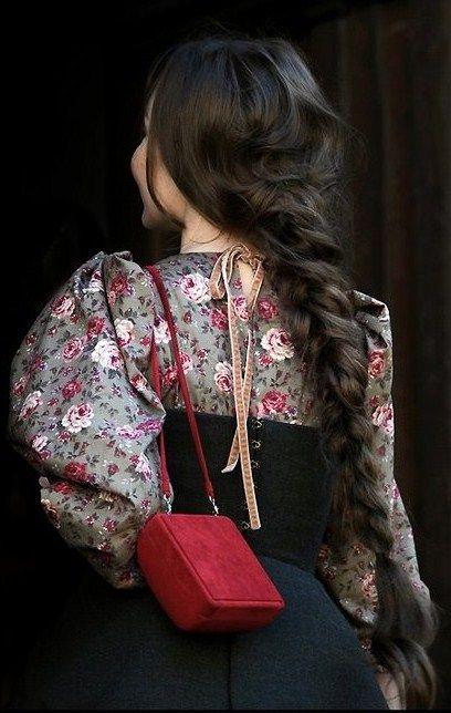 Ulyana Sergeenko, a fashion designer from Moscow. Blouse with folk Russian patterns and traditional Russian headdress – a long plait.