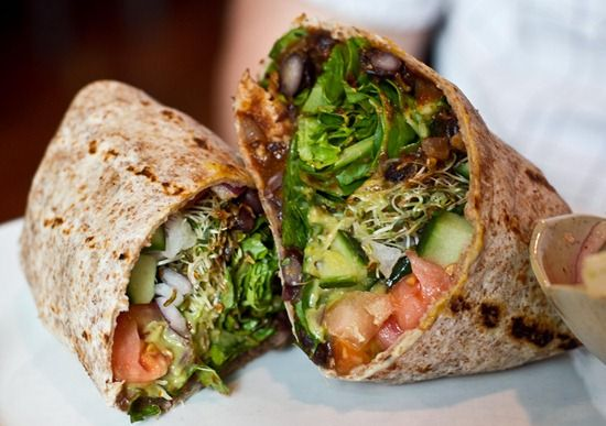 Black Bean Burrito made up of spicy black beans with chipolte avocado sauce, cilantro, tomato, lettuce, cucumber, red onion, & sprouts.