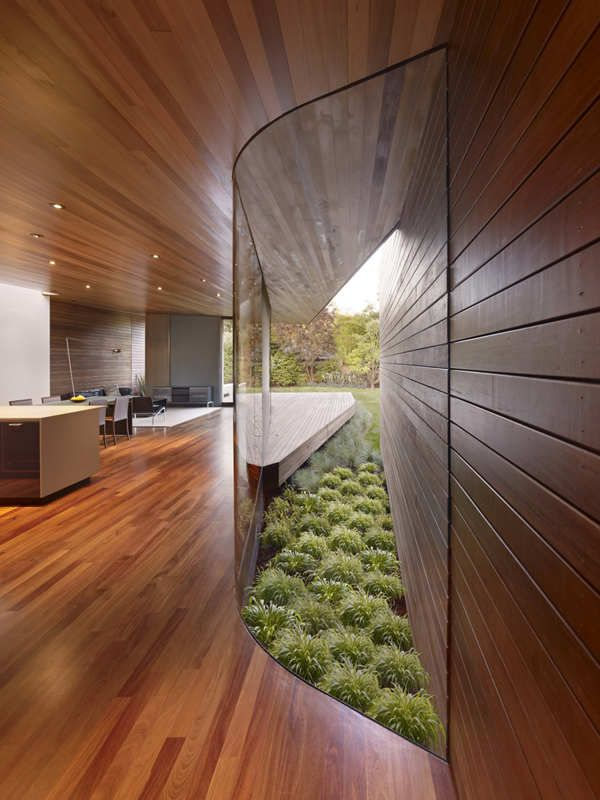 curved glass wall. very considered detail in the linear space