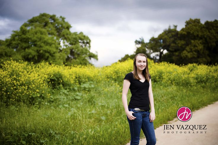 We love photographing kids ages of 5-15. Don't miss this important time as they change every day! Photographed at Bernal Ranch in San Jose, California- see our images on our website at jenvazquez.com | Real Kids by Jen Vazquez Photography - girl standing in front of grass with yellow mustard flowers and trees in background
