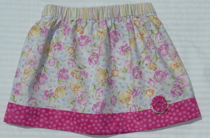 """""""Pink Poppies."""" This little skirt was made form scraps left over from a pinafore.  To get the length i used a contrasting fabric for the waistband.  The pink band on the hemline is from the Moda dot collection.  This is made in a Size 2."""