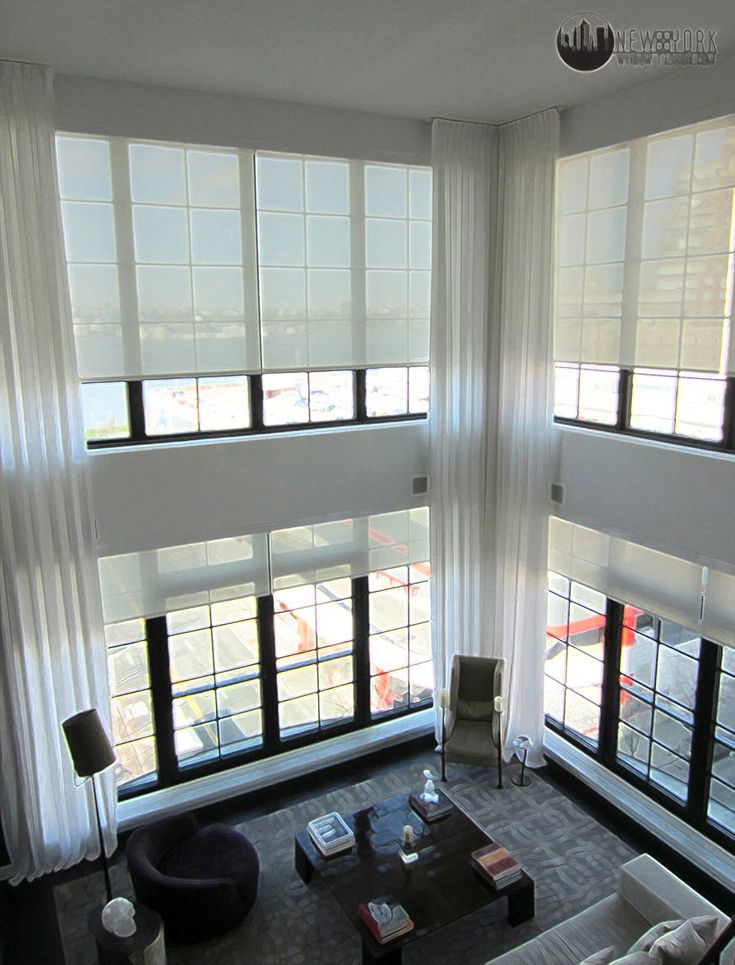 Double height white curtains emphasise the ceiling height for 2 way window blinds