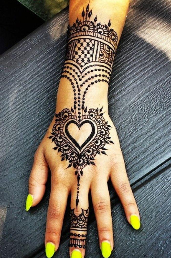 tattoo motive frau dezentes tattoo henna auf der hand von einer schönen frau gelbe nägel lackieren