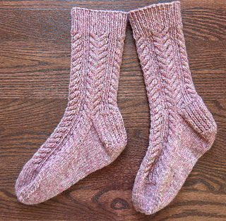 A warm and sturdy winter sock, with a simple cable to keep you from getting bored. These knit up quickly as the yarn is thicker than most sock yarn. They are fulled - not felted - which makes them warmer and softer.