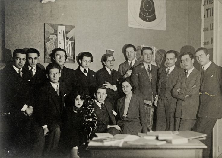 "Man Ray - Members of the ""bureau central de recherches surréalistes"" (1924) From left to right, standing: Jacques Baron, Raymond Queneau, Pierre Naville, André Breton, Jacques-André Boiffard, Giorgio de Chirico, Roger Vitrac, Paul Éluard, Philippe Soupault, Robert Desnos and Louis Aragon; seated: Simone Kahn Breton, Max Morise, Marie-Louise Soupault."