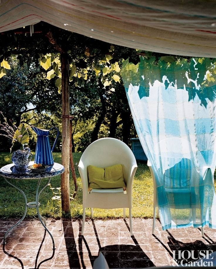 RUSTIC OUTDOOR SPACE BY DESIGNER'S GUILD A pergola covered with fabric shelters chairs by Philippe Starck in a Tuscan villa.
