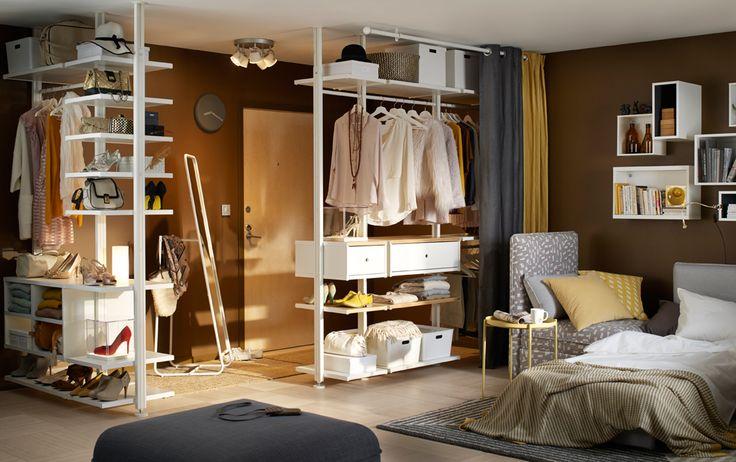 Kleine studio met plafondhoge opbergoplossing bestaande uit witte planken, lades en zijsteunen om kleding, tassen en schoenen op te bergen.
