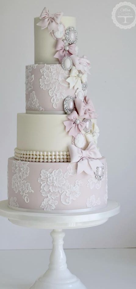 Mauve pink and cream wedding cake with handpainted lace and pearls. Adorned with sugar bows and broaches in silver, pink and white. #laceweddingcakes