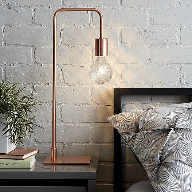 Shop arc copper table lamp.   Brilliant in its minimalist form, brushed copper-plated lamp suspends an exposed bulb in one sleek swoop.  Mint cloth cord adds fresh contrast.  We see it glowing bedside, on a bookshelf or on either end of a credenza.